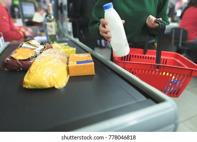 A girl presents products to the supermarket cash desk.