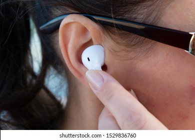 Girl pressing button on wireless earphones closeup.
