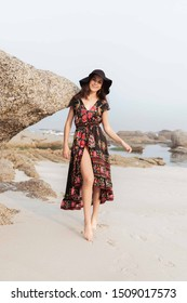 Girl in a pretty black dress at the beach with a hat on smiling and having fun