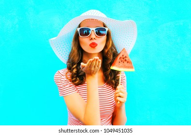 Girl pretty  sends an air kiss blowing red lips with a slice of watermelon ice cream a colorful blue background