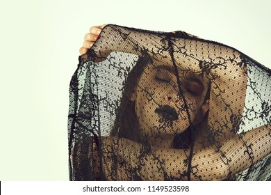 girl or pretty woman, fashionable model with closed eyes, stylish makeup, dark lips, lipstick, covering adorable face with black, lace veil on white background. Death, funeral, grief, mourning