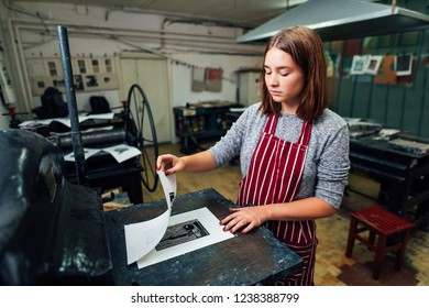 girl prints linocut on the machine