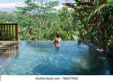 Girl in a private pool in Bali admires a beautiful view of the palm trees.Luxury holiday.Woman resting in the pool with a beautiful view of the palm trees on the island of Bali.Fruit in the pool