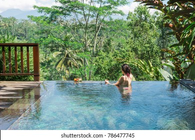 Girl in a private pool in Bali admires a beautiful view of the palm trees.Luxury holiday.Woman resting in the pool with a beautiful view of the palm trees on the island of Bali.Fruit in the pool.