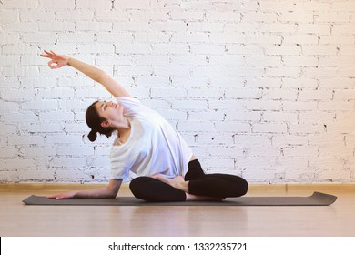The girl is a professional instructor of hatha yoga practicing asanas in the room against the background of a white brick wall. Lateral traction from Lotus pose (padmasana).
