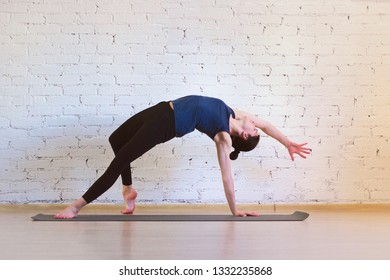 The girl is a professional instructor of hatha yoga practicing asanas in the room against the background of a white brick wall. Camatkarasana (Dancing dog pose or Wild thing).