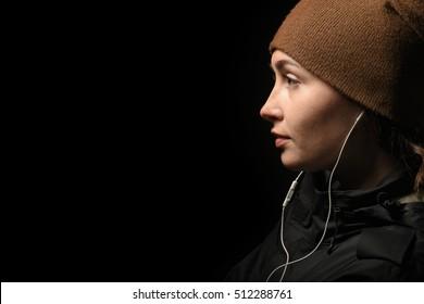 girl in profile, listening to music on headphones, dark background.