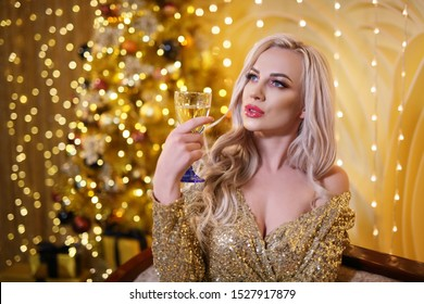 Girl with Prosecco wine . A glamorous model in a Golden dress holds a glass of champagne against the bright Christmas lights .