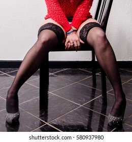Girl prostitute sitting on the chair in mini skirt, high heels and stockings.