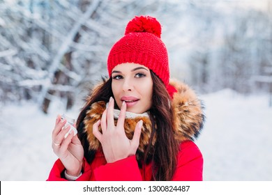 Girl protecting lips with lip balm in winter . Lips care