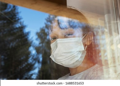 A girl in a protective medical mask looks out of the window. The girl is in quarantine because of the coronavirus