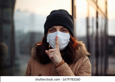 Girl in protective sterile medical mask on her face shows a gesture: shh. silence. The concept of preventing the spread of the epidemic and treating coronavirus, pandemic in quarantine city