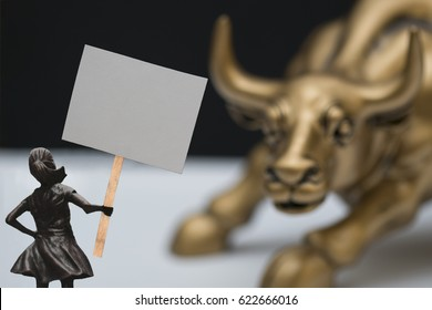 Girl with protest sign in front of bronze bull.  Sign is blank for customer to insert their own message.