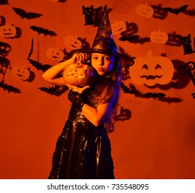 Girl with proud face on orange background with decor. Little witch wearing black hat. Halloween party and decorations concept. Kid in spooky witches costume in orange light holds carved jack o lantern