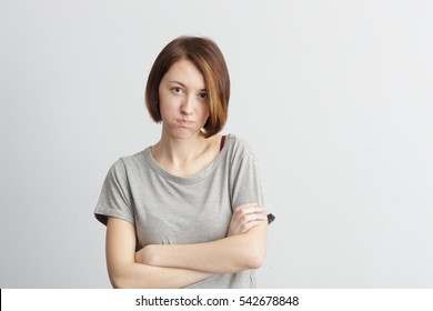 Girl puffed out her cheeks. She is offended and dissatisfied. Hands crossed