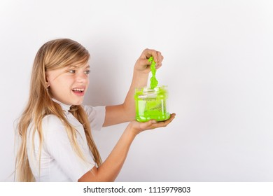 Girl pulling out a green slime from a plastic box