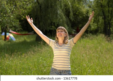 The girl pulls hands to the sun on a glade in wood