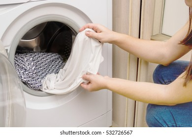 The girl pulls out clothes from the washing machine
