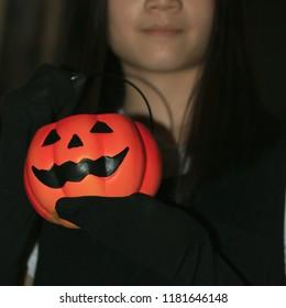 Girl and pumpkin on Halloween night