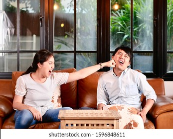 The girl punching the young man in the living room  In anger after an argument