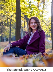 Girl in purple coat, blue jeans and white shirt is sitting on fallen yellow leaves in autumn park. Evening sunlight, contre-jour, glares.