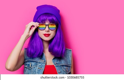Girl with purple hair and with rainbow eyeglasses on pink background