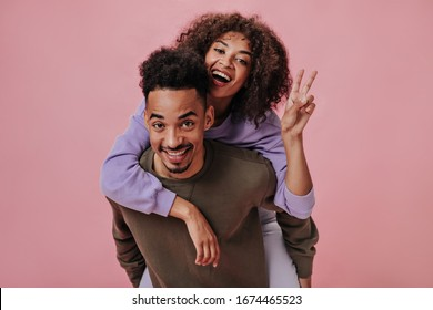 Girl in purple hoodie sitting on her boyfriends back and showing peace sign. Portrait of happy positive couple widely smiling on pink background
