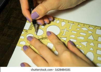 Girl with purple nails draws a circle with a ruler with figures