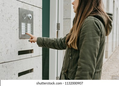 The girl pushes the doorphone button or calls the intercom