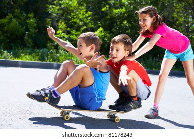 A girl pushing skateboard with two boys sitting on it