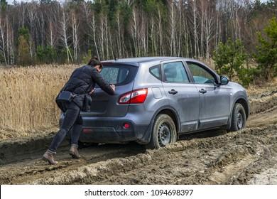 Girl pushing stuck car at swamp dirt road