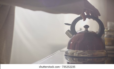 Girl put blue kettle on a kitchen gas stove. Stovetop whistling kettle in hand
