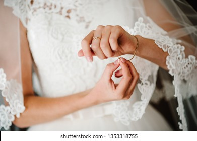 Girl put a bracelet on arm. bride putting on jewelry, focus on bracelet. Bridal preparation for the wedding ceremony.