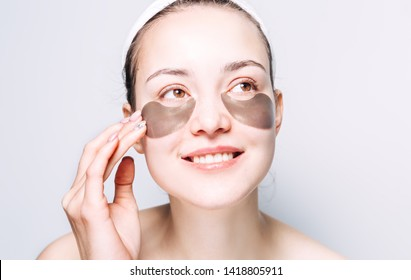 The girl put Korean hydrogel patches under her eyes and smiles