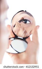 girl  put make up on eye close up reflection in mirror isolated on white