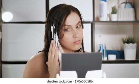 Girl puts foam on wet hair. Young attractive woman in bathroom looks in mirror and does hair styling by applying foam on her head. Makeup at home, hair care, hairstyle self concept. Close-up