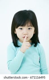 Girl puts her finger on lips, silence gesture