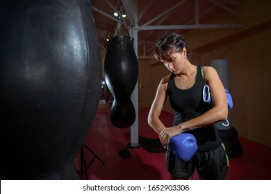 Girl puts on Boxing gloves in the sport gym. Sports, training, motivation, active lifestyle concept.