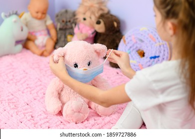 The girl puts on a medical mask for a teddy pink bear. The girl plays at home on the topic of coronavirus.