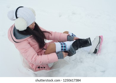 Girl puts on skates outdoors at winter