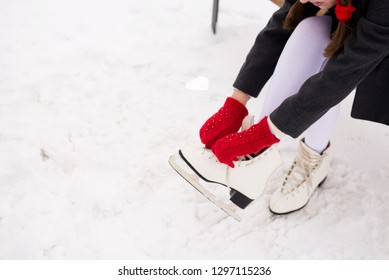 girl puts on white figure skates in the park
