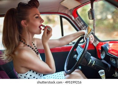 girl putting on lipstick while driving