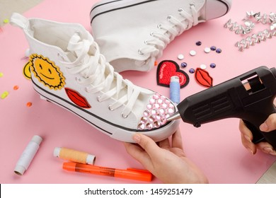 Girl putting rhinestones on sneakers with a hot glue gun. Customization of favorite shoes.