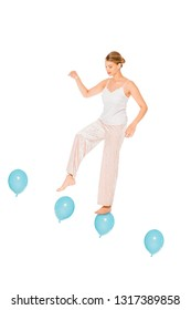 girl in pyjamas levitating in air and standing on ballons isolated on white