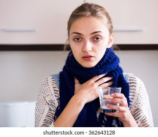 Girl with quinsy taking medicine and gargling throat in kitchen
