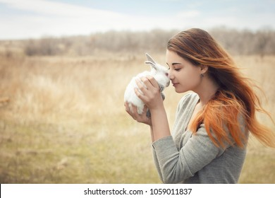 the girl with the rabbit.happy little girl holding cute fluffy Bunny.Friendship with Easter Bunny. Spring photo with beautiful young girl with her Bunny. Girl is holding a cute little rabbit