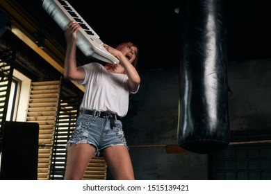 the girl in a rage beats a musical instrument on a punching bag