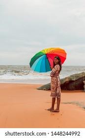 Girl with rainbow umbrella at honey beach Gokarna