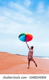 Girl with rainbow umbrella jumping floating at honey beach Gokarna