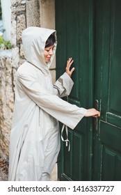 Girl in a raincoat in front of the green door